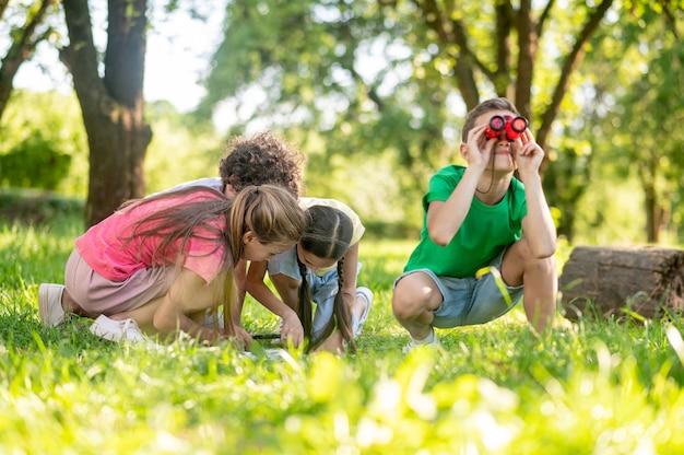 Jongen met verrekijker en vrienden in de buurt van kaart