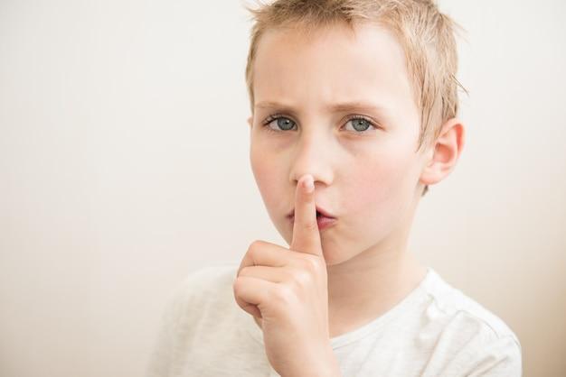 Jongen met vinger op lippen die een stil gebaar maken