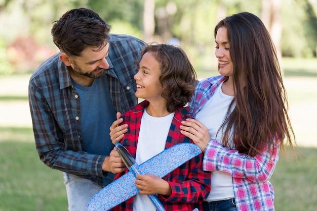 Jongen met vliegtuig en ouders samen in het park