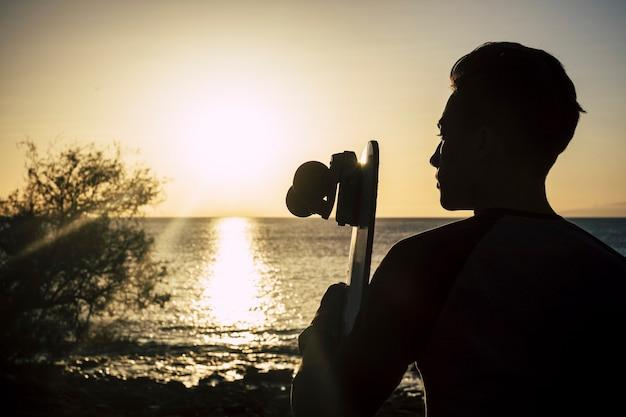 Jongen met zijn skateboard bij de zonsondergang zittend op het strand kijkend naar de zee en de lucht - vrijheid levensstijl concept - mooie tiener