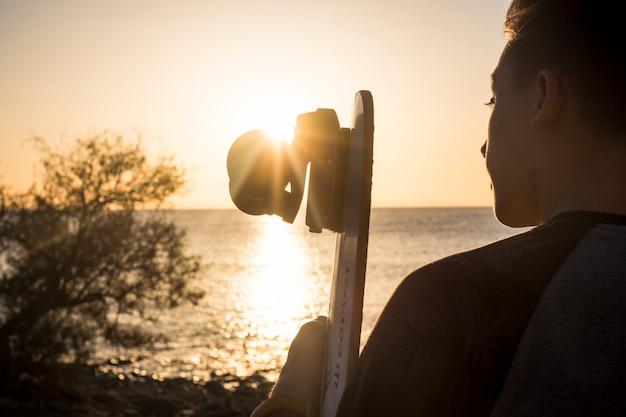 Jongen met zijn skateboard bij de zonsondergang zittend op het strand kijkend naar de zee en de lucht - vrijheidslevensstijlconcept