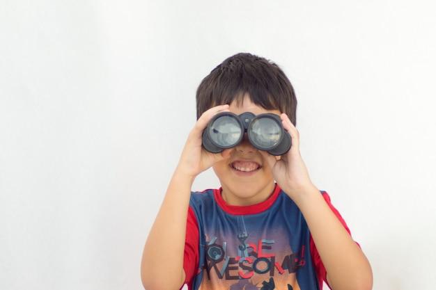 Jongen met zwarte verrekijker die de camera onder ogen ziet die in blauw en rood overhemd op witte achtergrond glimlacht