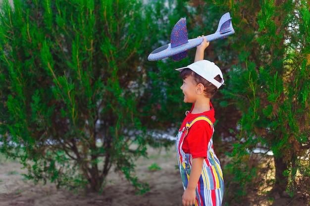 Jongen met zweefvliegtuig in zijn handen een kind speelt met een vliegtuig op straat in het park buiten spelen b...