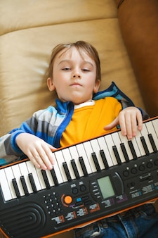 Jongen moe van het leren spelen van de synthesizer