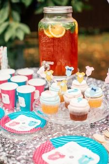 Jongen of meisjescake en verschillende traktaties voor baby showerpartij op lijst in openlucht