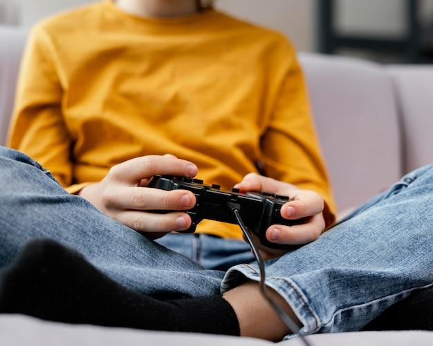 Jongen op bank met joysticks spelen