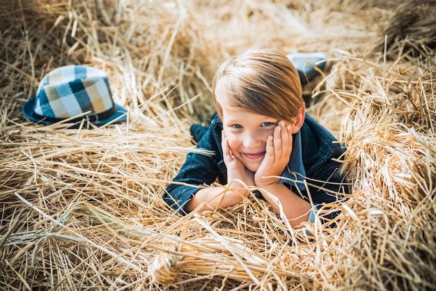 Jongen op een briesje in een herfstdorp herfstkinderen met herfststemming herfsttijd voor kindermodeverkoop