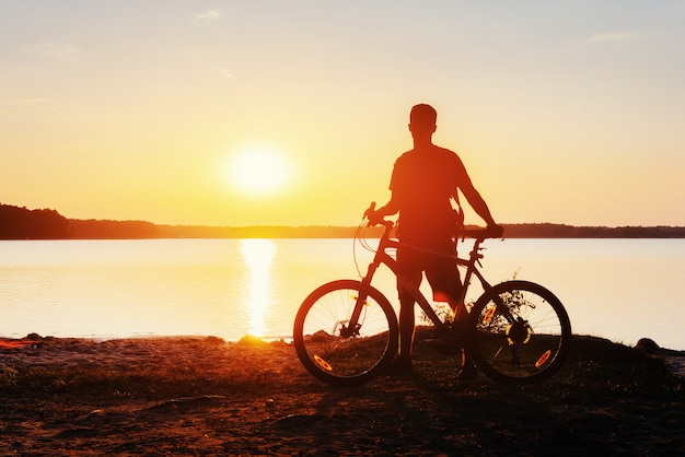 Jongen op een fiets bij zonsondergang Premium Foto