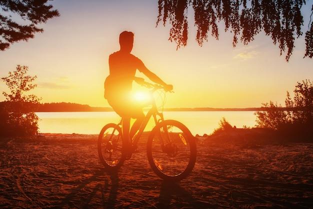 Jongen op een fiets bij zonsondergang