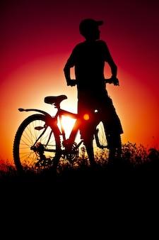 Jongen op een fiets op de zonsondergangachtergrond
