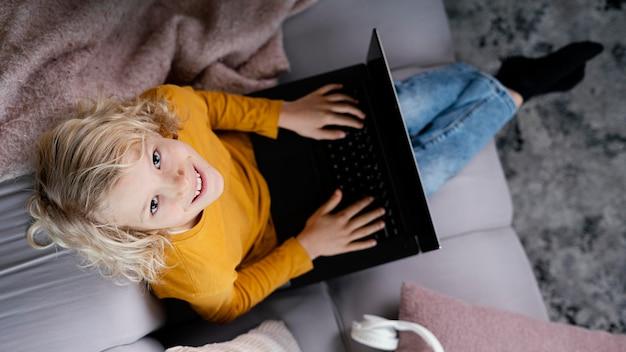 Jongen op laag met laptop