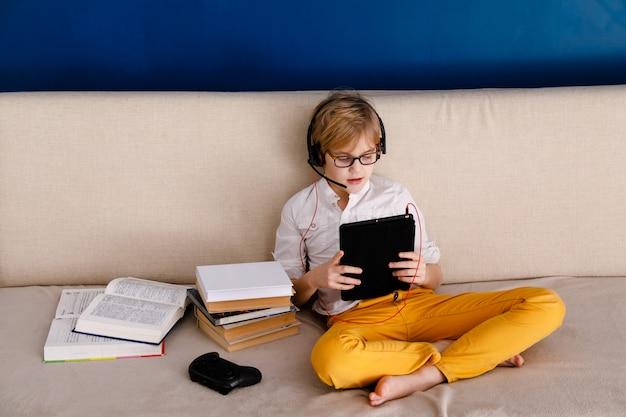 Jongen op zelfisolatie met behulp van digitale tablet voor huiswerk, voor het zoeken van informatie over internet, sociale afstand, het leren van online onderwijs. gezondheidszorg concept.