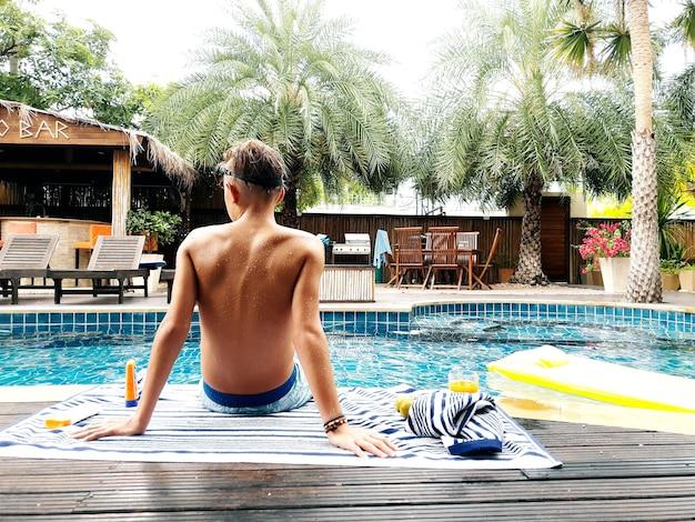 Jongen opknoping bij het zwembad