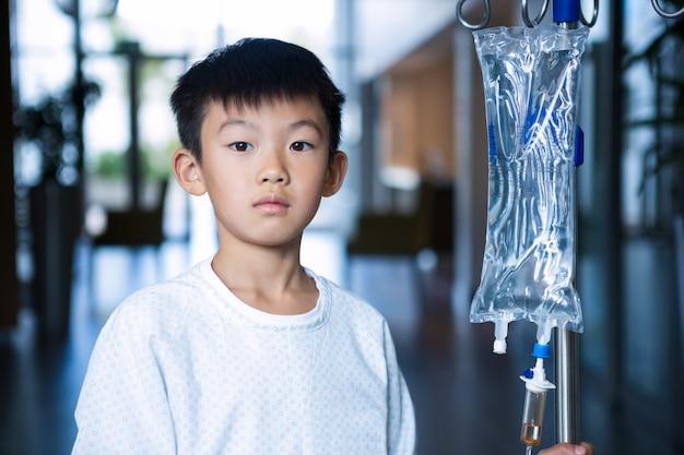 Jongen patiënt met intraveneuze iv infuusstandaard in gang