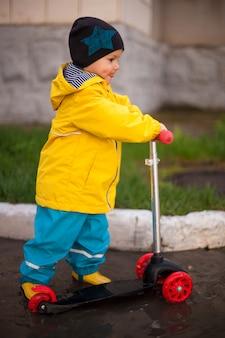 Jongen, peuter in rubberen laarzen die op een scooter door de plassen rijdt, veer, verhard, stak met plezier zijn tong uit. blij kind