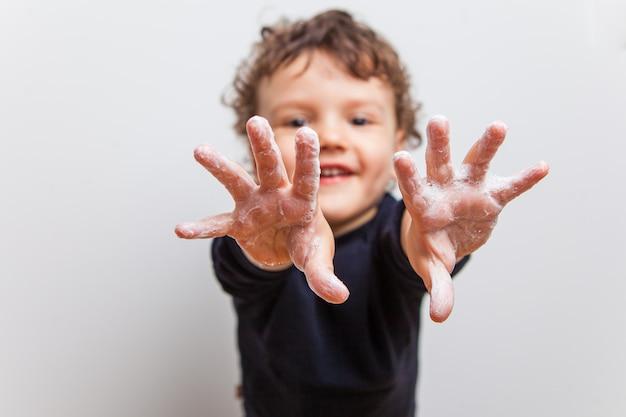 Jongen, peuter trekt gezeepte handen naar voren