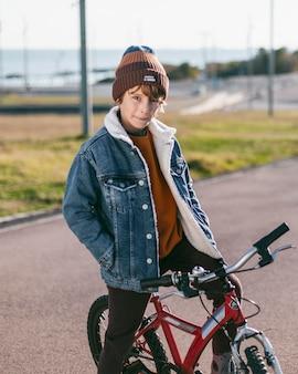 Jongen poseren tijdens het rijden met zijn fiets in de stad