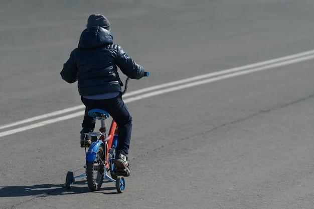 Jongen rijdt op een fiets achteraanzicht op een wandelweg