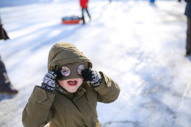 Jongen rodelen op straat in de besneeuwde winter in de bergen