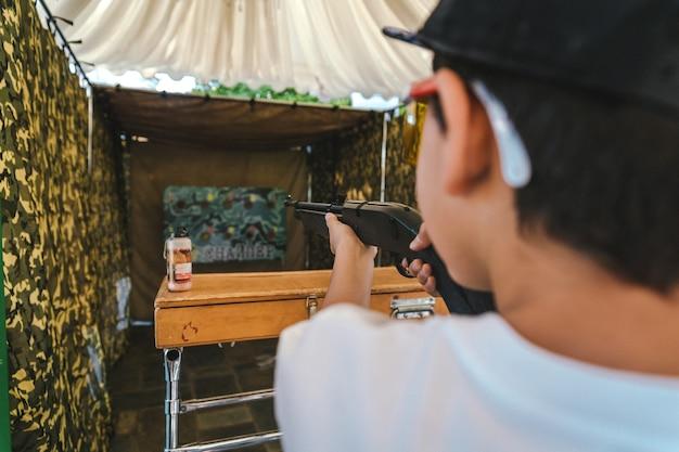 Jongen schiet een luchtgeweer in het dashboard.