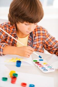 Jongen schilderij. kleine jongen ontspannen tijdens het schilderen met aquarellen aan tafel