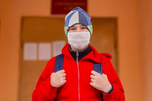Jongen schooljongen loopt de school uit met een beschermend masker