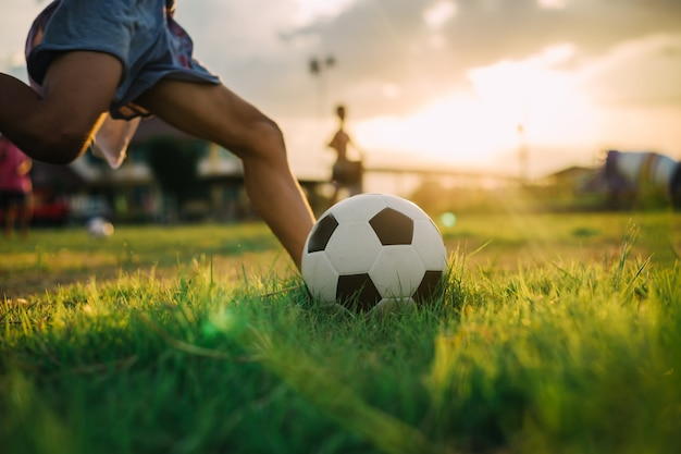 Jongen schopt een bal met blote voet tijdens het spelen van straatvoetbal voetbal op het groene grasveld
