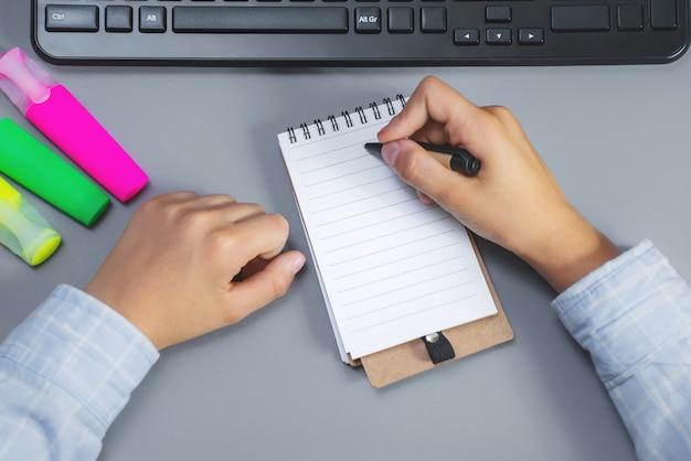 Jongen schrijft in een notitieblok op een desktop.
