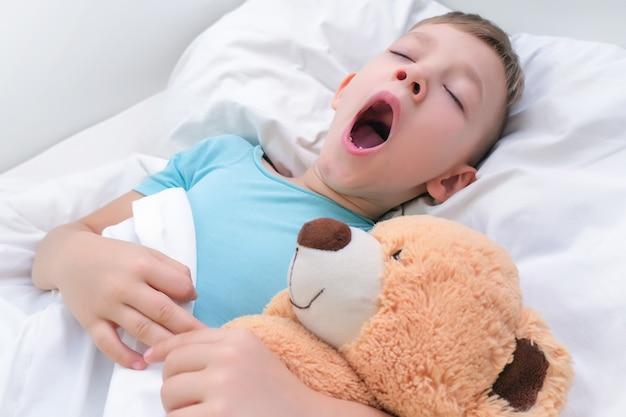 Jongen slaapt met zacht stuk speelgoed teddybeer, kind gaapt