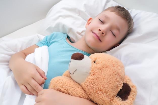 Jongen slaapt zoet knuffelend een speelgoedbeer