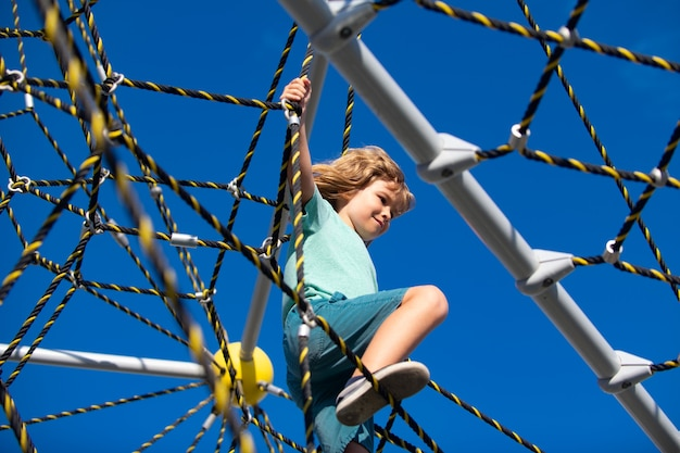 Jongen speelt in de speeltuin kinderen spelen buiten touwpark