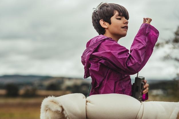 Jongen speelt in het bos en gekleed in een waterpak of regenjas op een regenachtige dag die probeert te communiceren via gps met zijn gps-telefoon
