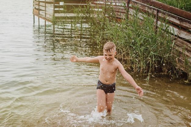 Jongen speelt in het water op de oever van een meer. zomervakantie.