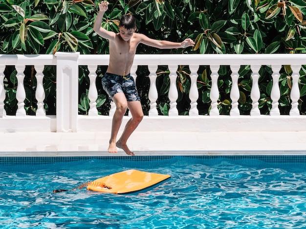 Jongen speelt in het zwembad door op een kleine surfplank te springen om hun evenwicht te bewaren