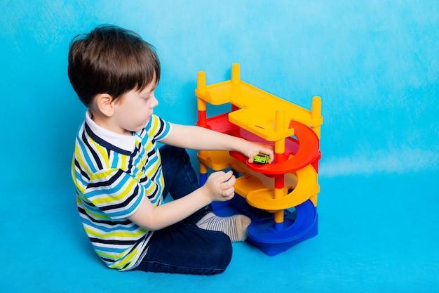 Jongen speelt met auto's in speelgoed parkeren op blauwe achtergrond