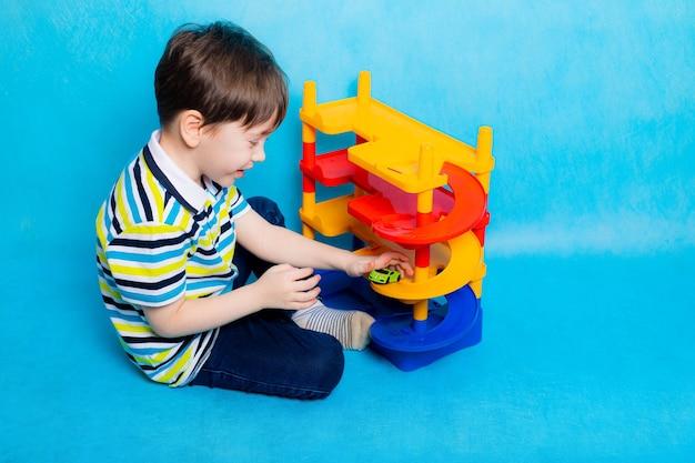 Jongen speelt met auto's op de parkeerplaats. speelgoed voor kinderen. een jongen speelt het spel parkeren op een blauwe ondergrond bright parking voor auto's. gelukkige jeugd