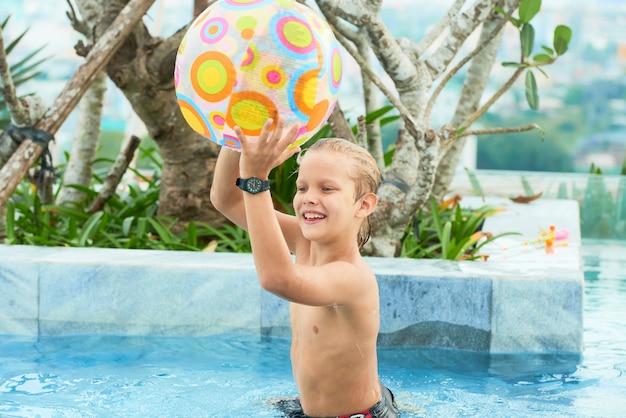 Jongen speelt met de bal in het zwembad