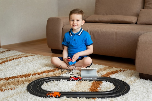 Jongen speelt met de racebaan op de afstandsbediening op het tapijt