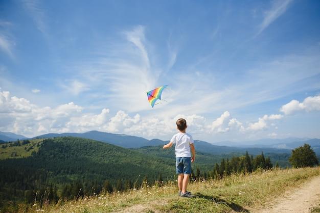 Jongen speelt met een vlieger in de bergen