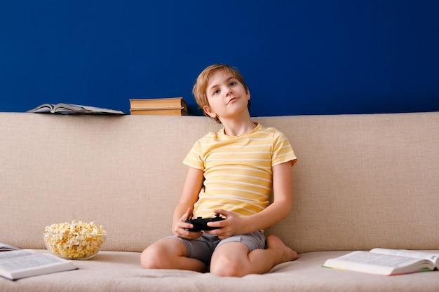 Jongen speelt met gamepad in plaats van lessen en eet popcorn