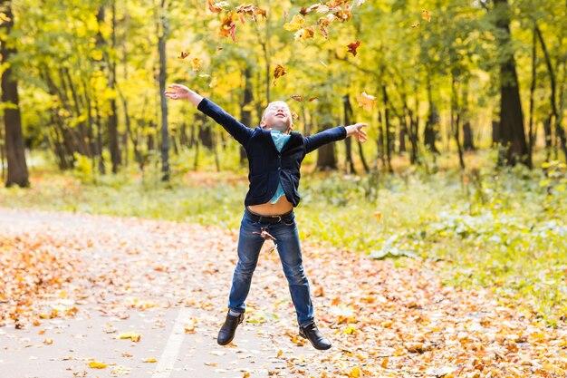 Jongen speelt met herfstbladeren in het park