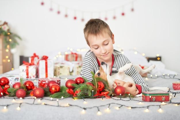 Jongen speelt met hond jack russell op een bed met de decoratie van het nieuwe jaar