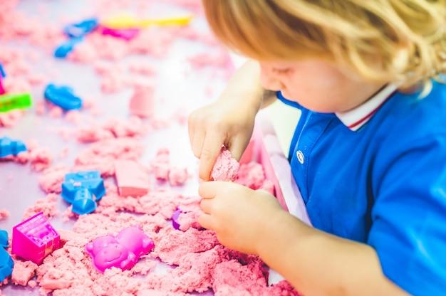 Jongen speelt met kinetisch zand in de kleuterschool
