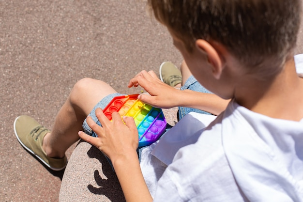 Jongen speelt met regenboog anti-stress pop-it speelgoed buiten