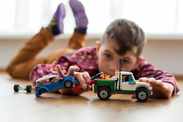Jongen speelt met speelgoedauto's. kind spelen op de vloer. kinderpret overdag. blij om thuis te zijn.