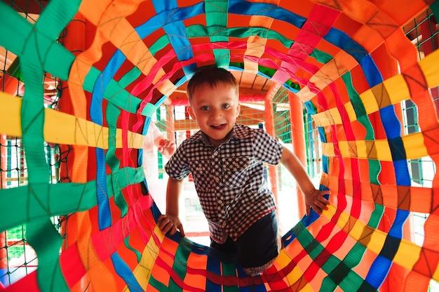 Jongen speelt op de speelplaats, in het doolhof van de kinderen. labyrint voor kinderen.