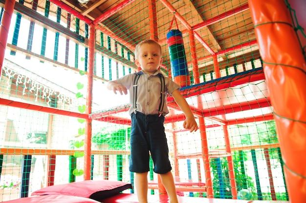 Jongen speelt op de speelplaats, in het doolhof van de kinderen.