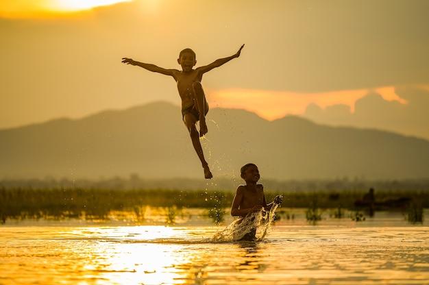 Jongen speelt plonswater in de rivier tijdens zonsondergang, plonswater, thailand
