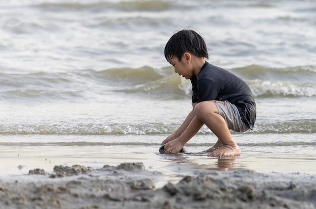 Jongen spelen aan de zee op een vakantie strandvakantie