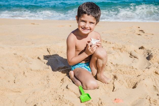Jongen spelen met shell op het strand